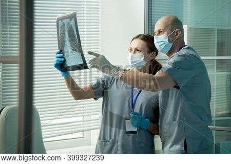 Bald male clinician in uniform and protective mask and gloves pointing at lung x-ray held by his assistant during discussion of pathologies