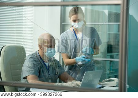 Young female assistant or clinician in protective workwear pointing at laptop display while standing by colleague scrolling through data