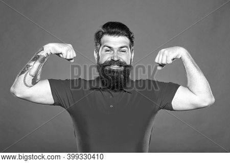 Mens Power. Happy Hipster Fix Arms Red Background. Bearded Man Show Muscle Power. Power Training. Ph