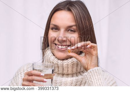 Vitamins And Food Supplements. Close Up Of Happy Smiling Woman Holding A Glass Of Water And Taking A