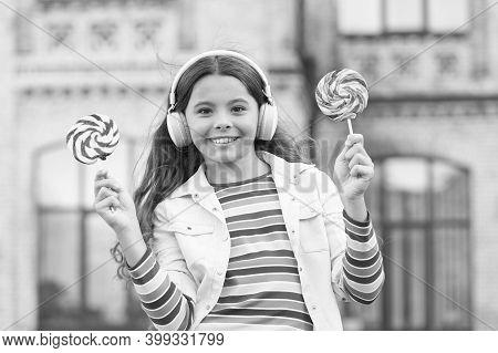 Her Favorite Sweet. Girl In Headphones. Little Girl In Wireless Headset With Lollipop. Back To Schoo