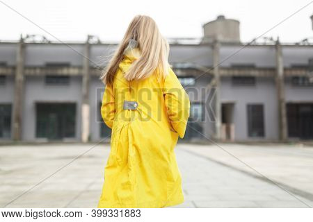 Little Caucasian Girl 7 Years Old With Blonde Hair In Yellow Raincoat From Behind. Colors Of The Yea