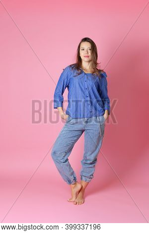 Full-length Portrait Of A Smiling European Young Woman In A Blue Shirt And Jeans Hiding Her Hands In