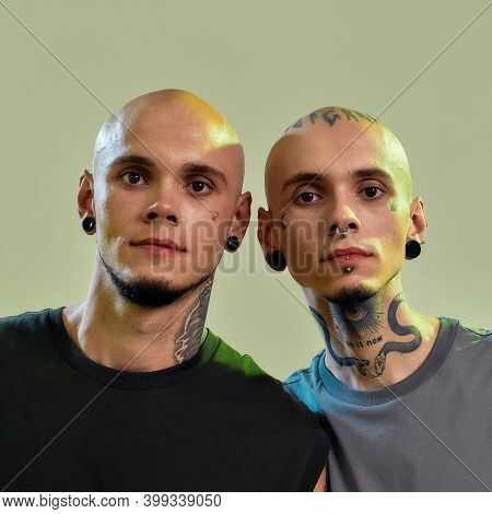 Close Up Portrait Of Two Young Men, Twin Brothers With Tattoos And Piercings Looking At Camera, Posi