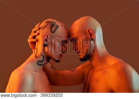 Portrait Of Young Twin Brothers With Tattoos And Piercings Standing Head To Head, Looking At Each Ot
