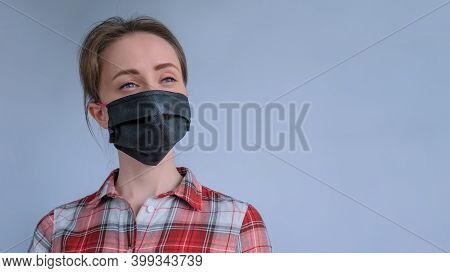 Portrait Of Woman Wearing Black Medical Face Mask, Red Plaid Shirt, Looking Away In Room With Grey W