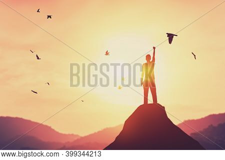 Freedom Feel Good And Travel Adventure Concept. Copy Space Of Silhouette Man Rising Hands On Sunset