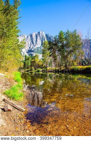 Charming little lake in the Yosemite Valley. Yosemite Park is located on the slopes of the Sierra Nevada. The rock-monolith El Capitan is reflected in the smooth water.