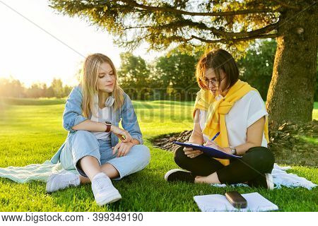 Female Teacher Psychologist Social Worker Talking To Teenage Student On The Lawn In The Park. Sociol