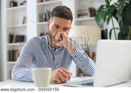Concentrated Modern Business Man Analyzing Data Using Laptop While Working In The Office.