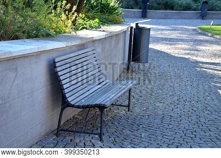 A Bench With A Gray Paneled Seat By The Retaining Wall On A Granite Cube Sidewalk In A City Park And