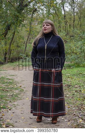 Proud Adult Self-assured Woman Strolls Through Park In Early Fall. Middle-aged Woman With Long Loose