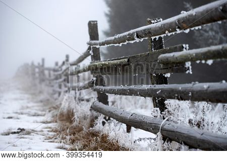 Frosty, frozen wooden fence in misty winter landscape covered with snow.