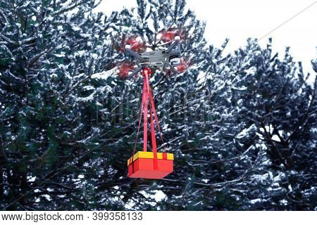 A Drone. Flies With A Christmas Gift Against The Background Of A Snow-covered Forest.