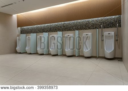 A Row Of Urinals In Tiled Wall In A Public Restroom. Empty Man Toilet
