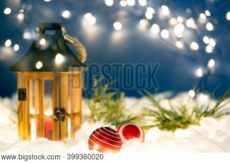 Christmas lantern on snow with fir branch and Christmas decorations in evening scene