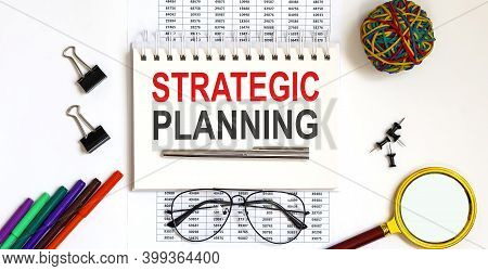 Notebook With Strategic Planning Word With Office Tools On White Table.