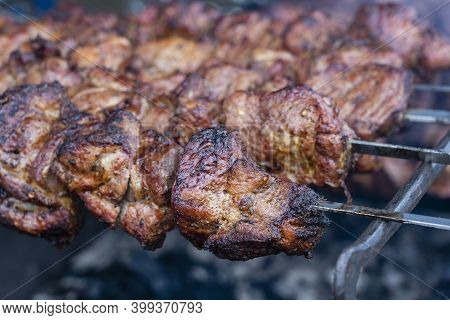 Grilled Kebab Cooking On Metal Skewer Closeup. Roasted Meat Cooked At Barbecue. Bbq Fresh Beef Meat