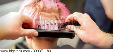 Close Up Back View Of Hairdressers Hands Straightening Short Pink Hair With A Hair Iron Straightener