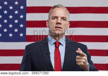 Front View Portrait Of Mature Politician Giving Speech And Gesturing While Standing Against Usa Flag