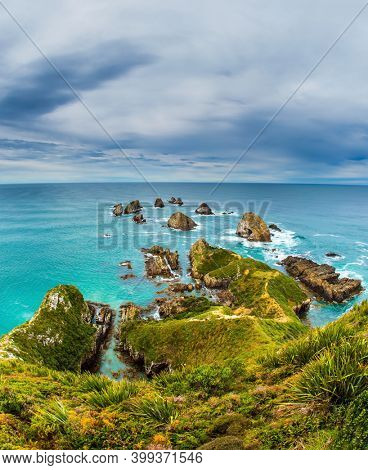South Island, New Zealand. The picturesque coast of the Pacific Ocean near Nugget Points. Big stones - rocks along the shore in the ocean surf. The concept of active, environmental and photo tourism