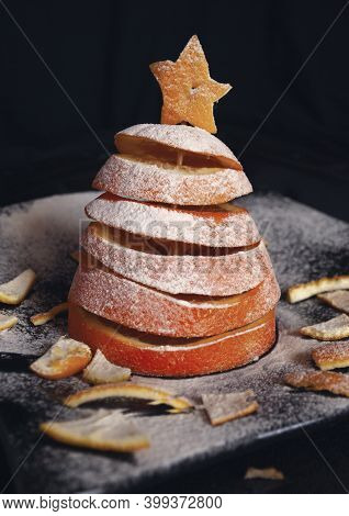 Christmas Tree Made Of Sliced ​​orange Sprinkled With Powdered Sugar. Pieces Of Orange Peel Around T