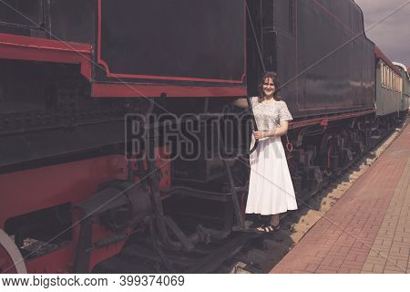 A Girl Stands On The Steps Of The Cars Train. The Vintage Train Is At The Station. Embarkation Or Di