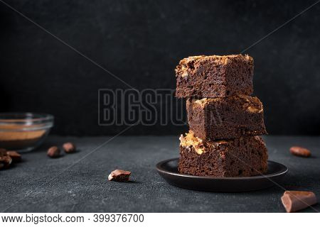 Stack Of  Brownies On Black Background. Delicious Homemade Chocolate Dessert, Brownie With Peanut Bu