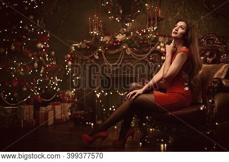 Christmas and New Year. Beautiful happy girl celebrates Christmas in the fairy Christmas interior with lights around. Christmas tree and fireplace in the background.