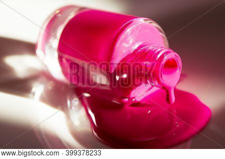 Pink Nail Polish Dripping From Bottle. Natural Hard Light, Deep Shadows. The Concept Of Fashion And