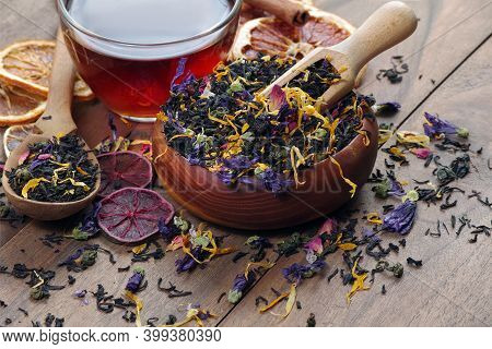 Blended Tea. Black Tea With Dry Flower Petals And Citrus Fruits. Dry Black Tea Leaves In A Wooden Sc