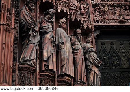 Ancient Priest Statue And Ruin Building Of Strasbourg Church Or The Cathedral Of Our Lady Of Strasbo