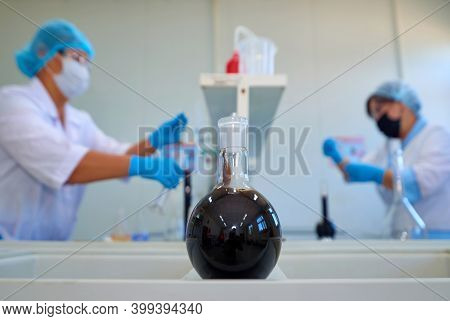 Laboratory Flask With Crude Oil. Lab Test  Petroleum In The Background.