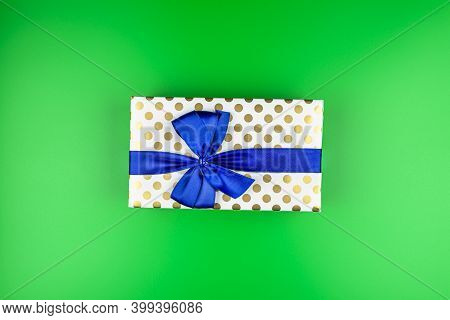 A Gift Wrapped In White Paper With Gold Circles Wrapped In A Blue Ribbon Tied In A Bow, Isolated On