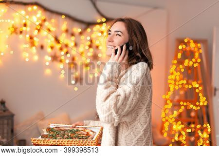 Photo Of A Young Lady Is Ordering Pizza While Talking On The Phone.