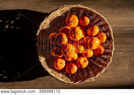 Oranges In A Wicker Basket, Sun Shines To Create Light And Shadow, Top View.