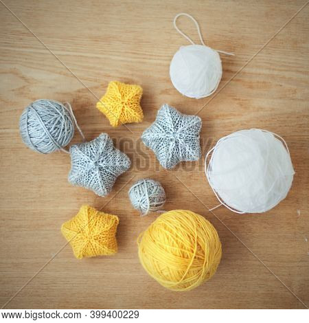 Christmas Decor, Noel Ornament. Knitted Stars. Yellow, Gray, White Stars, Clew Yarn On The Wooden Ba