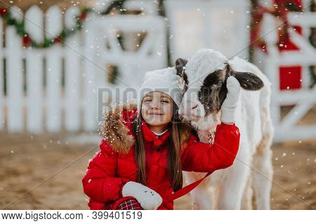 Pretty Young Girl In Red Winter Jacket, White Hat And Squared Pants Posing With Young Black And Whit