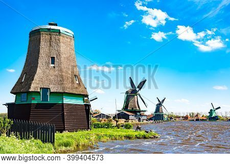 Dutch Typical Landscape. Traditional Old Dutch Windmills Against Blue Cloudy Sky In The Zaanse Schan