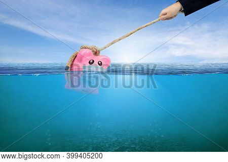 Financial Aid And Rescue From Debt Problems For Investments Above Water As A Drowning Pink Piggy Ban