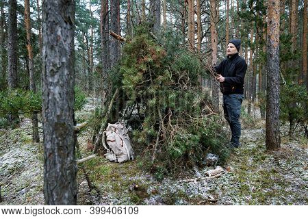 Wilderness Survival Camp - Man Building Tree Branch Hut In Forest In Winter