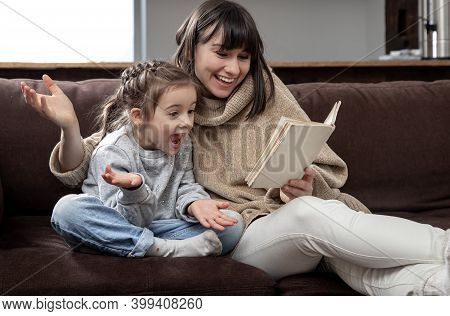 Mom And Daughter Spend Time Together Reading A Book. The Concept Of Children's Development And Quali
