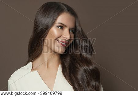Healthy Brunette Model Woman With Long Curly Hair Smiling On Brown Background, Fashion Beauty Portra
