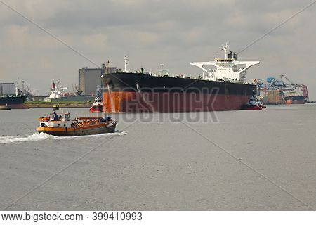 Large crude oil tanker ship pumping out ballast water when coming into port in Rotterdam, tug boat pushing the side