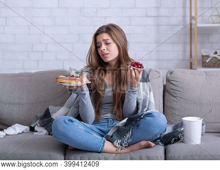 Eating Disorders Concept. Stressed Young Woman Devouring Sweets On Couch At Home, Full Length Portra