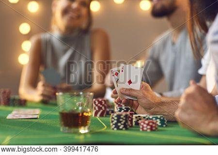Ace And King Aka Big Slick In Hand Of Man Sitting At Card Table Among Friends Playing Poker