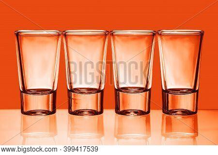 Four Vodka Shots Isolated On Orange. Vodka Glass In A Row. Orange Booze Liquor. Weekend Party Symbol