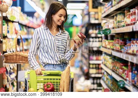 Portrait Of Smiling Woman With Shopping Cart In Supermarket Buying Groceries Food Walking Along The