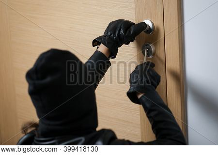 Thief Broke Into The Apartment. House Robbery By Woman In A Black Jacket And Black Mask. Burglar In