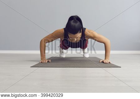 Athletic Woman Does Push-ups To Warm Up The Pectoral Muscles, Triceps And Shoulders.